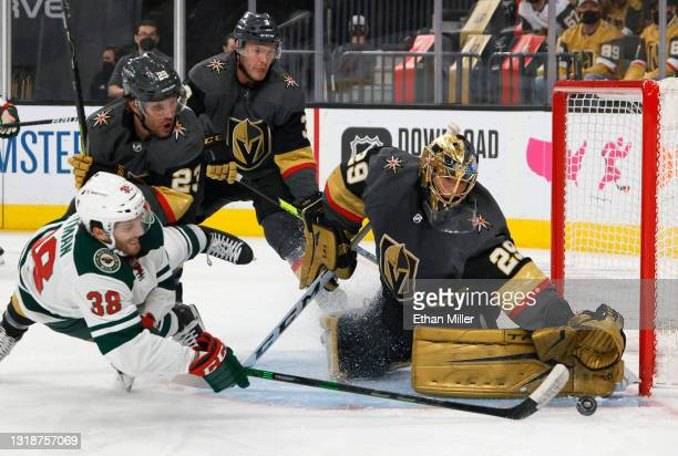 Marc-Andre Fleury of the Vegas Golden Knights defends the net against Ryan Hartman of the Minnesota Wild as he is tripped by Alec Martinez of the...