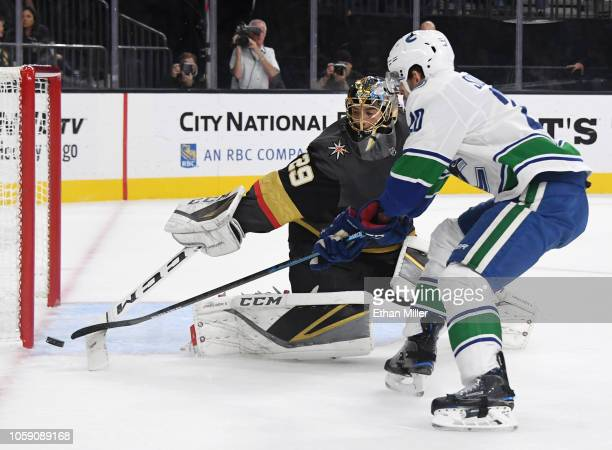 Marc-Andre Fleury of the Vegas Golden Knights knocks the puck away from Brandon Sutter of the Vancouver Canucks in the first period of their game at...