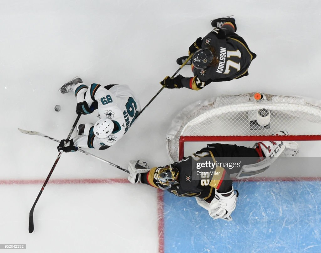 Marc-Andre Fleury #29 of the Vegas Golden Knights knocks the puck away from Mikkel Boedker #89 of the San Jose Sharks as William Karlsson #71 of the Golden Knights defends in the first overtime period of Game Two of the Western Conference Second Round during the 2018 NHL Stanley Cup Playoffs at T-Mobile Arena on April 28, 2018 in Las Vegas, Nevada. The Sharks won 4-3 in double overtime.
