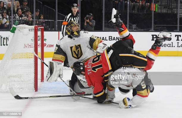 Marc-Andre Fleury of the Vegas Golden Knights looks on as Matthew Tkachuk of the Calgary Flames falls over Deryk Engelland of the Golden Knights in...