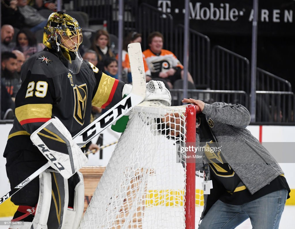 Marc-Andre Fleury #29 of the Vegas Golden Knights looks on as Vegas Golden Knights ice operations manager George Salami fixes a goal-line camera in the net in the third period of the Golden Knights' game against the Philadelphia Flyers at T-Mobile Arena on February 11, 2018 in Las Vegas, Nevada. The Flyers won 4-1.