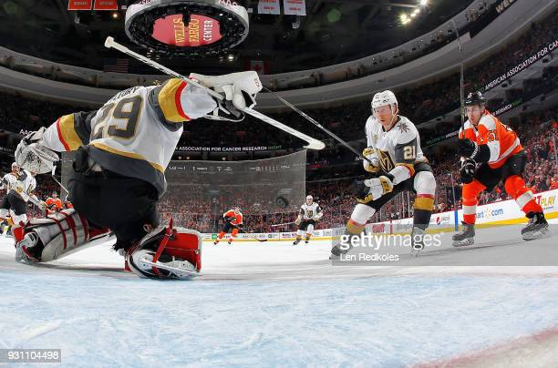MarcAndre Fleury of the Vegas Golden Knights makes a stick save as Cody Eakin protects the airborn puck from Valtteri Filppula of the Philadelphia...