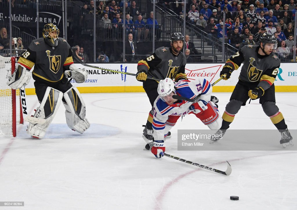 Marc-Andre Fleury #29 of the Vegas Golden Knights tends net as David Desharnais #51 of the New York Rangers falls to the ice going after the puck in front of Deryk Engelland #5 and Shea Theodore #27 of the Golden Knights in the third period of their game at T-Mobile Arena on January 7, 2018 in Las Vegas, Nevada. The Golden Knights won 2-1.