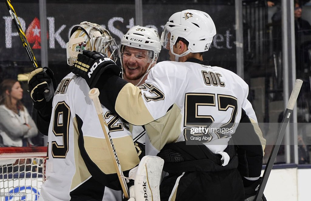 Marc-Andre Fleury #29, Zach Sill #38 and Marcel Goc #57 of the Pittsburgh Penguins celebrate the teams win over the Toronto Maple Leafs during NHL game action October 11, 2014 at the Air Canada Centre in Toronto, Ontario, Canada.