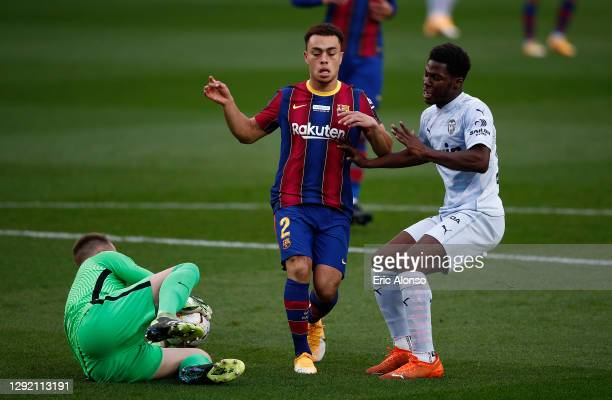 Marc-Andre ter Stegen of FC Barcelona collects the ball from the feet of Yunus Musah of Valencia CF as Sergino Dest of FC Barcelona blocks off during...