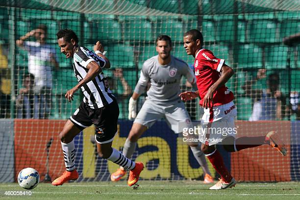 Marcao of Figueirense run into the area with Ernando of Internacional during a match between Figueirense and Internacional as part of Campeonato...