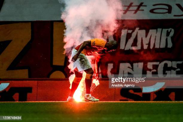 Marcao of Galatasaray picks up a torch thrown in the pitch during the Turkish Super Lig week 3 derby match between Galatasaray and Fenerbahce at Turk...