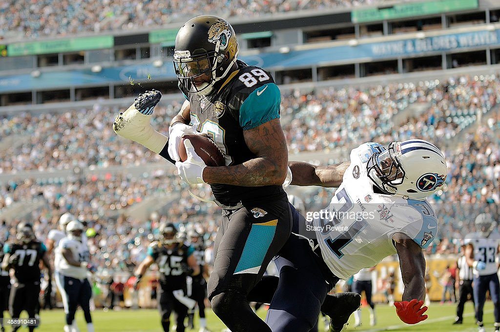 Marcedes Lewis #89 of the Jacksonville Jaguars catches a touchdown pass over Bernard Pollard #31 of the Tennessee Titans during a game at EverBank Field on December 22, 2013 in Jacksonville, Florida.