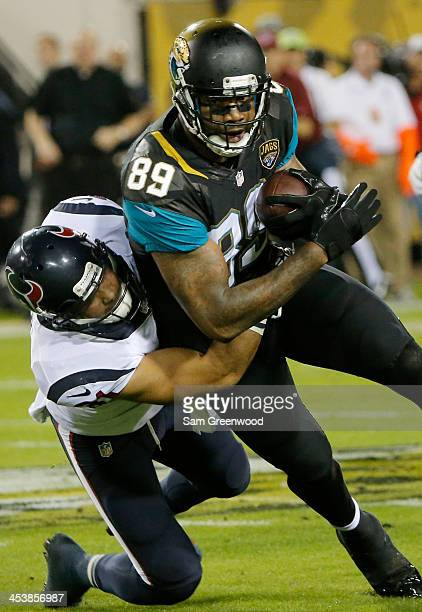 Marcedes Lewis of the Jacksonville Jaguars is tackled by Darryl Sharpton of the Houston Texans during the game at EverBank Field on December 5 2013...