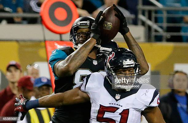 Marcedes Lewis of the Jacksonville Jaguars make a reception against Darryl Sharpton of the Houston Texans during the game at EverBank Field on...