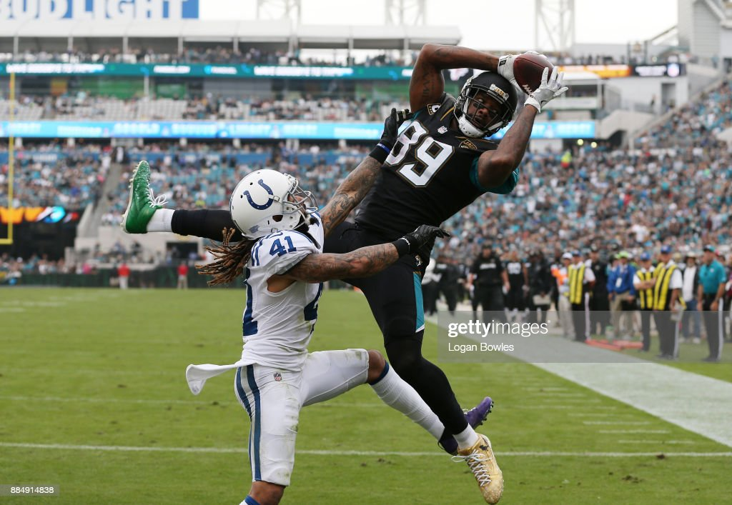 Marcedes Lewis #89 of the Jacksonville Jaguars makes a catch over Matthias Farley #41 of the Indianapolis Colts in the second half of their game at EverBank Field on December 3, 2017 in Jacksonville, Florida.