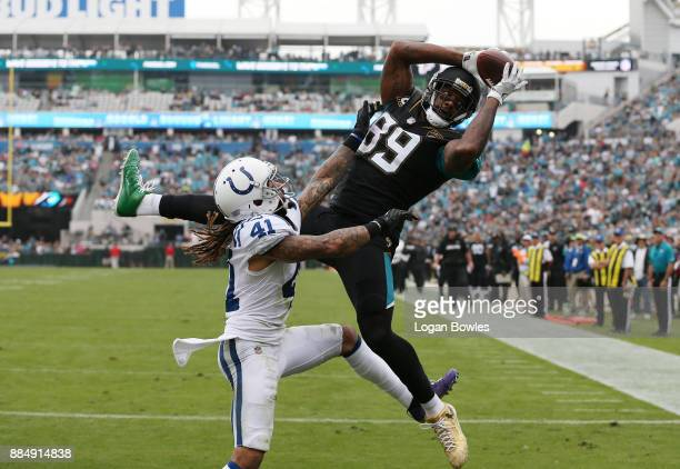 Marcedes Lewis of the Jacksonville Jaguars makes a catch over Matthias Farley of the Indianapolis Colts in the second half of their game at EverBank...