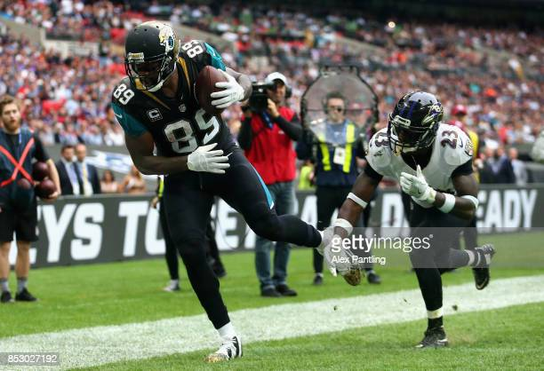Marcedes Lewis of the Jacksonville Jaguars scores a touchdown under pressure from Tony Jefferson of the Baltimore Ravens during the NFL International...