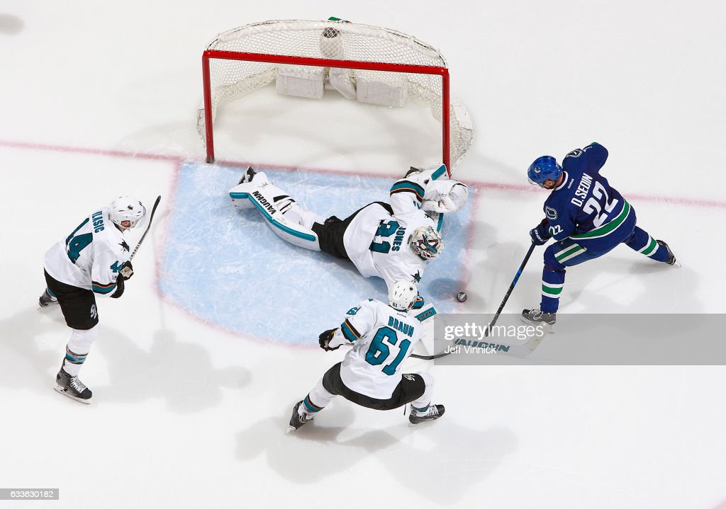 Marc-Edouard Vlasic #44 and Justin Braun #61 of the San Jose Sharks look on as Martin Jones #31 of the San Jose Sharks makes a save off the shot of Daniel Sedin #22 of the Vancouver Canucks during their NHL game at Rogers Arena February 2, 2017 in Vancouver, British Columbia, Canada. San Jose won 4-1.