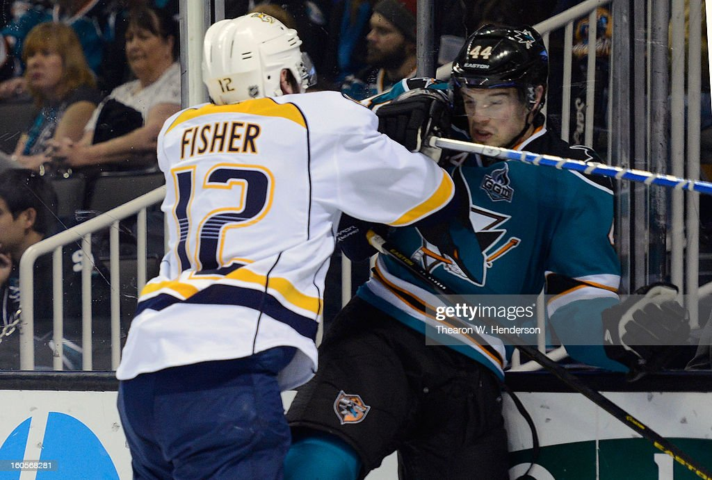 Marc-Edouard Vlasic #44 of the San Jose Sharks gets checked up against the boards by Mike Fisher #12 of the Nashville Predators in the first periord of their game at HP Pavilion on February 2, 2013 in San Jose, California.
