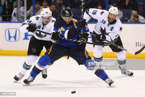 MarcEdouard Vlasic of the San Jose Sharks looks to keep TJ Oshie of the St Louis Blues off the puck at the Scottrade Center on October 15 2013 in St...