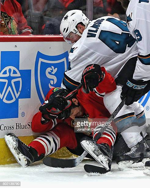 MarcEdouard Vlasic of the San Jose Sharks pressures Andrew Desjardins of the Chicago Blackhawks who sits on the puck at the United Center on December...