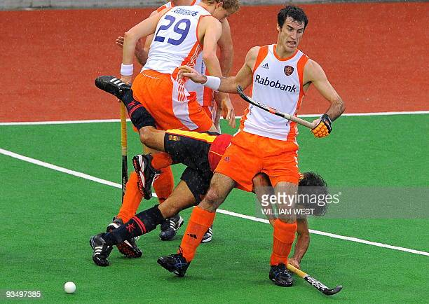 Marcel Balkestein and Tim Jenniskens of the Netherlands tackle Spain's Eduard Arbos during their Champions Trophy field hockey match played in...