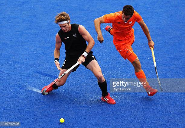 Marcel Balkestein of The Netherlands challenges Andrew Hayward of New Zealand during the Men's Hockey preliminary match between The Netherlands and...