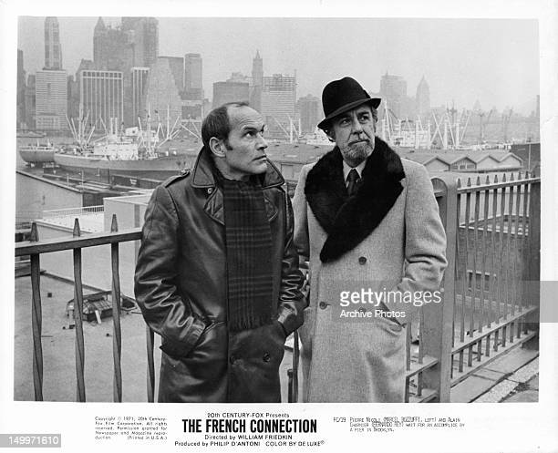Marcel Bozzuffi and Fernando Rey wait for an accomplice by a pier in Brooklyn in a scene from the film 'The French Connection' 1971