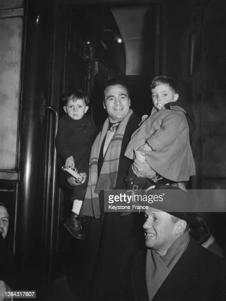 Marcel Cerdan et ses enfants Marcel Jr et René, en partance pour l'Angleterre puis les Etats-Unis, à la gare du Nord à Paris en France, le 27 février...