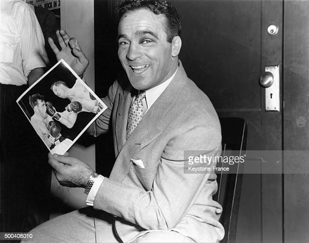 Marcel Cerdan in the offices of the Champions tournament, he is holding a picture taken during the match at the end of which he became World...