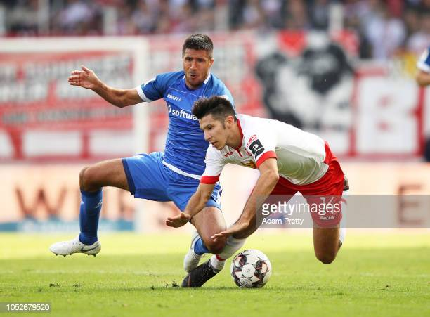 Marcel Correia of Jahn Regensburg is tackled by Slobodan Medojevic of SV Darmstadt 98 during the Second Bundesliga match between SSV Jahn Regensburg...