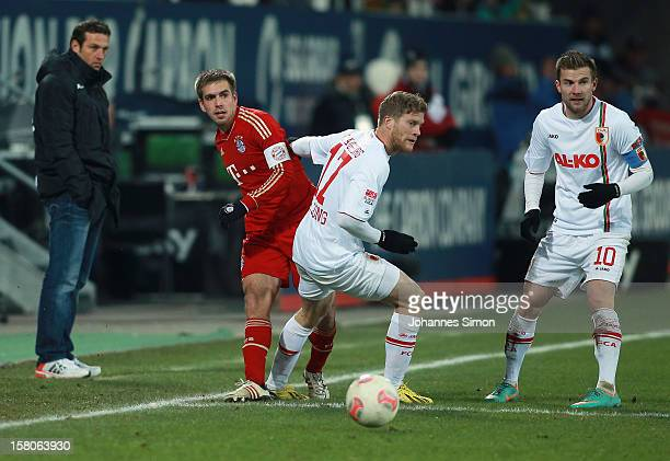 Marcel de Jong of Augsburg fights for the ball with Philipp Lahm of Bayern watched by Markus Weinzierl headcoach of Augsburg and Daniel Baier of...