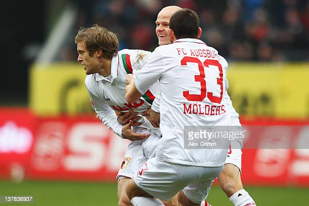 Marcel de Jong of Augsburg with team mates Tobias Werner and Sascha Moelders celebrates his team's first goal during the Bundesliga match between FC...