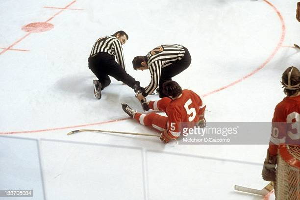 Marcel Dionne of the Detroit Red Wings sits on the ice as he and the linesman had their skates locked together during the game in March 1972