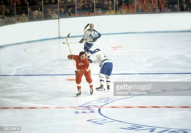 Marcel Dionne of the Detroit Red Wings tries to avoid the check by Billy MacMillan of the Toronto Maple Leafs during their game on March 8, 1972 at...