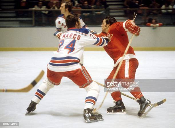 Marcel Dionne of the Detroit Red Wings tries to get around a check by Ab DeMarco of the New York Rangers circa 1972 at the Madison Square Garden in...