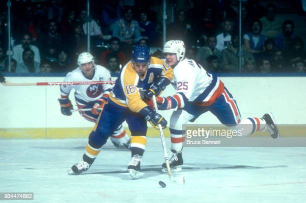 Marcel Dionne of the Los Angeles Kings skates with the puck as Ari Haanpaa of the New York Islanders defends during an NHL game circa 1985 at the...
