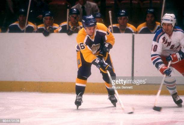 Marcel Dionne of the Los Angeles Kings skates with the puck as he is defended by Mark Pavelich of the New York Rangers during an NHL game on October...