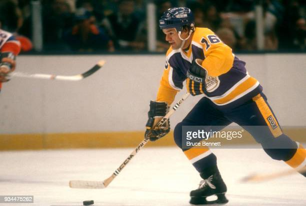 Marcel Dionne of the Los Angeles Kings skates with the puck during an NHL game against the New York Islanders circa 1983 at the Nassau Coliseum in...
