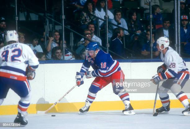 Marcel Dionne of the New York Rangers skates with the puck as Brad Lauer and Bob Bassen of the New York Islanders defend during an NHL game circa...