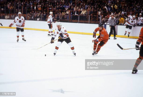 Marcel Dionne of the Wales Conference and Los Angeles Kings skates with the puck as Wayne Gretzky of the Campbell Conference and Edmonton Oilers...