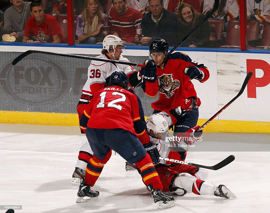 Marcel Goc #57 and Jack Skille #12 of the Florida Panthers tangle with Jussi Jokinen #36 and Riley Nash #20 of the Carolina Hurricanes at the BB&T Center on March 3, 2013 in Sunrise, Florida.