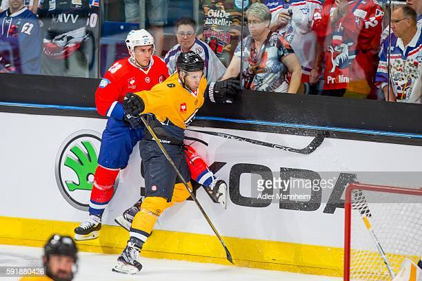 Marcel Goc of Adler is checked into the boards by Massimo Ronchetti of HC Lugano during the Champions Hockey League match between Adler Mannheim and...