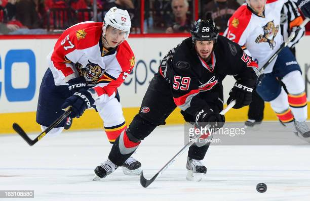 Marcel Goc of the Florida Panthers races to the puck against Chad LaRose of the Carolina Hurricanes during an NHL game on March 2 2013 at PNC Arena...