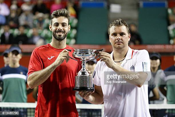 Marcel Granollers of Spain and Marcin Matkowski of Poland pose with a trophy after winning the men's doubles final match against Raven Klaasen of...