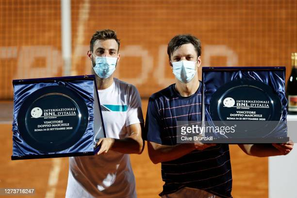 Marcel Granollers of Spain and playing partner Horacio Zeballos of Argentina pose with their trophies after winning the men's doubles final against...