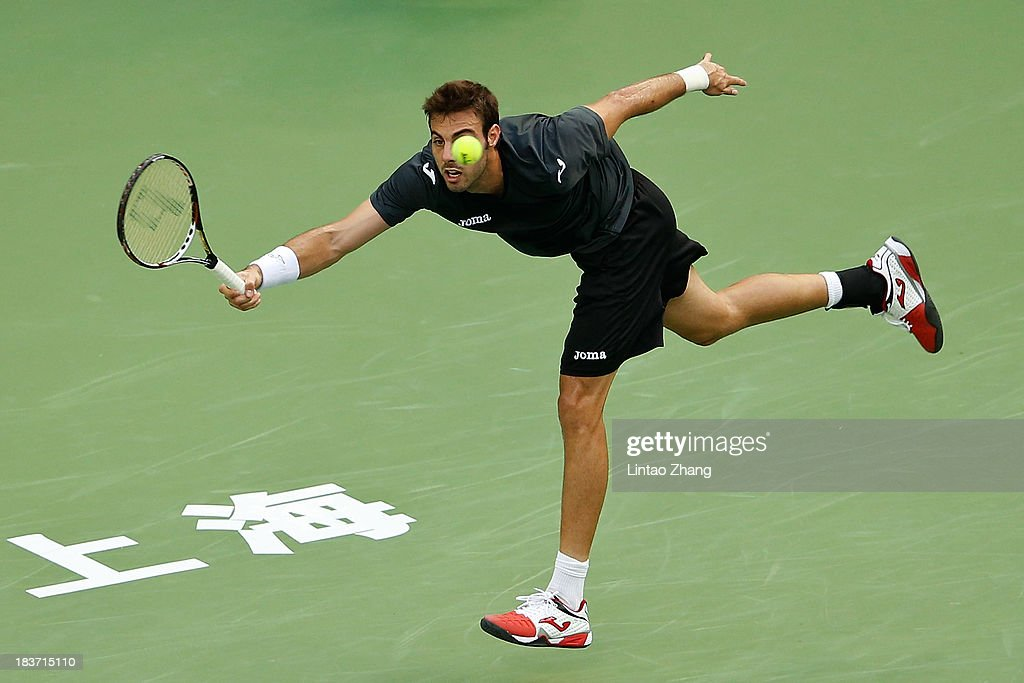 Marcel Granollers of Spain returns a shot to Novak Djokovic of Serbia during day three of the Shanghai Rolex Masters at the Qi Zhong Tennis Center on October 9, 2013 in Shanghai, China.
