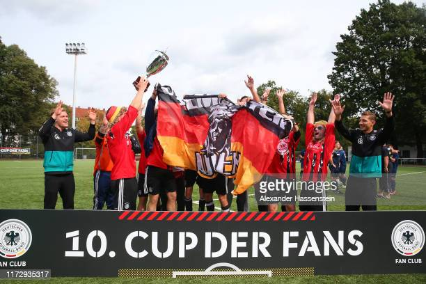 "Marcel Halstenberg and Niklas Stark hands-over the winners trophy to the team of Luenemuenster Luden after winning the ""10. Cup der Fans"" Tournament..."