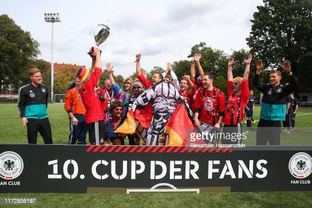 "Marcel Halstenberg hands-over the winners trophy to the team of Luenemuenster Luden after winning the ""10. Cup der Fans"" Tournament at..."