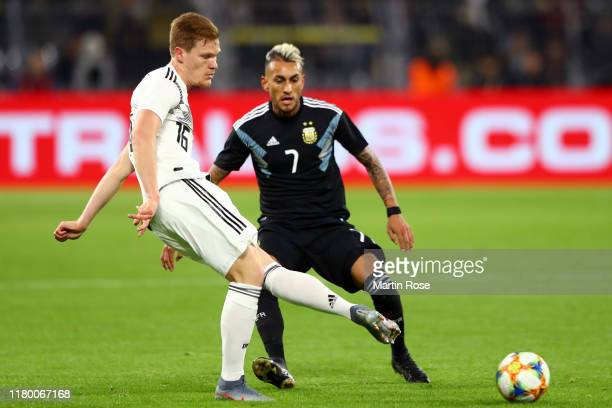 Marcel Halstenberg of Germany passes the ball under pressure from Roberto Pereyra of Argentina during the International Friendly match between...
