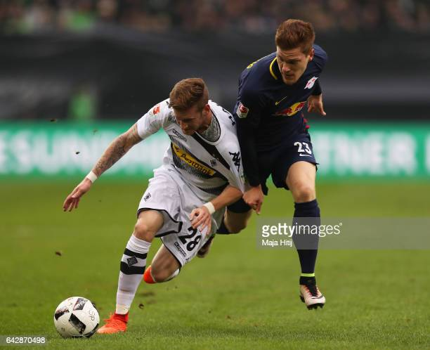 Marcel Halstenberg of Leipzig is challenged by Andre Hahn of Gladbach during the Bundesliga match between Borussia Moenchengladbach and RB Leipzig at...