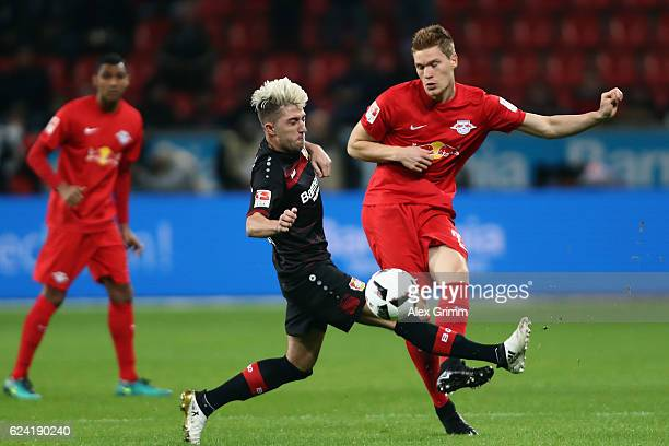Marcel Halstenberg of Leipzig is challenged by Kevin Kampl of Leverkusen during the Bundesliga match between Bayer 04 Leverkusen and RB Leipzig at...
