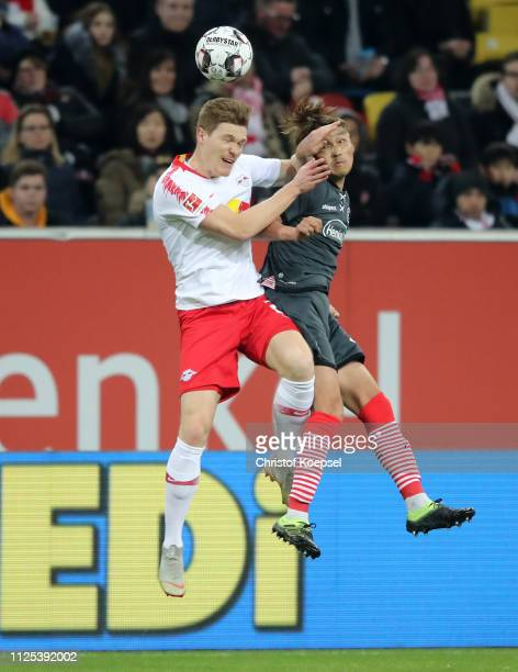 Marcel Halstenberg of RB Leipzig and Takashi Usami of Fortuna Duesseldorf jump for the ball during the Bundesliga match between Fortuna Duesseldorf...