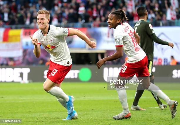 Marcel Halstenberg of RB Leipzig celebrates with Christopher Nkunku after scoring his team's fourth goal during the Bundesliga match between RB...